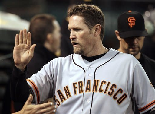 San Francisco Giants' Aubrey Huff is congratulated after scoring against the Oakland Athletics during the fourth inning of an exhibition baseball game Tuesday, April 3, 2012, in Oakland, Calif. Huff scored on a single by Brandon Belt. (AP Photo/Ben Margot)