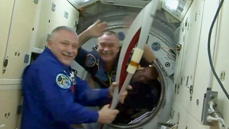In this image made from video provided by NASA, cosmonaut Fyodor Yurchikhin, International Space Station commander, holds the Sochi 2014 Winter Olympics torch brought aboard by fellow cosmonaut Mikhail Tyurin as Tyurin, Rick Mastracchio of the United States and Koichi Wakata of Japan enter the station on Thursday, Nov. 7, 2013. The crew plans to carry the unlit torch around the station's numerous modules before taking it out on a spacewalk. (AP Photo/NASA)
