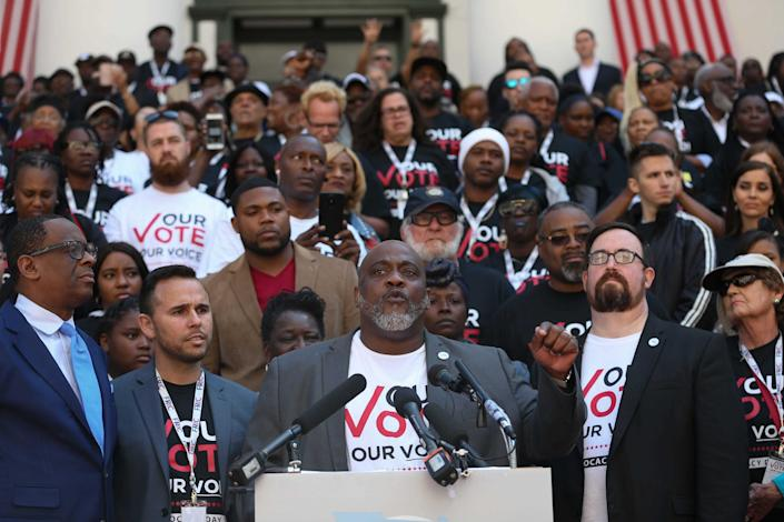 Desmond Meade, the president of the Florida Rights Restoration Coalition (center), speaks in front of Floridians with felony convictions on March 12, 2020, in Tallahassee, Fla. Voters passed a constitutional amendment in 2018 designed to give them their right to vote, but in September 2020, the 11th Circuit Court of Appeals upheld a state law that requires them to repay all courts fees, fines and restitution before they can vote.