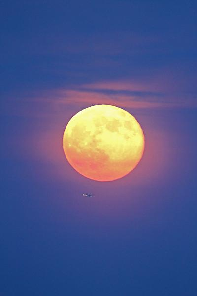 Veteran night sky photographers Edwin Aquirre and Imelda Joson took this amazing photo of the supermoon full moon rising through haze over downtown Boston on June 23, 2013.