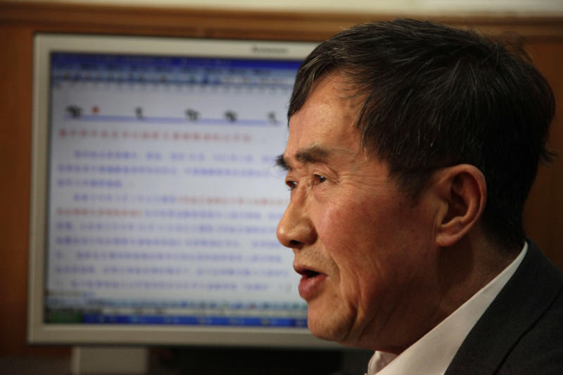 Chen Bingzhong, 78, formerly head of a government health research and outreach agency, speaks near a computer screen showing the open letter he issued that is circulating on the Internet in Beijing Tuesday, Nov. 30, 2010. Chen is calling on the government to come clean about a 1990s blood-selling scandal that infected tens of thousands of people with the virus that causes AIDS. (AP Photo/Ng Han Guan)