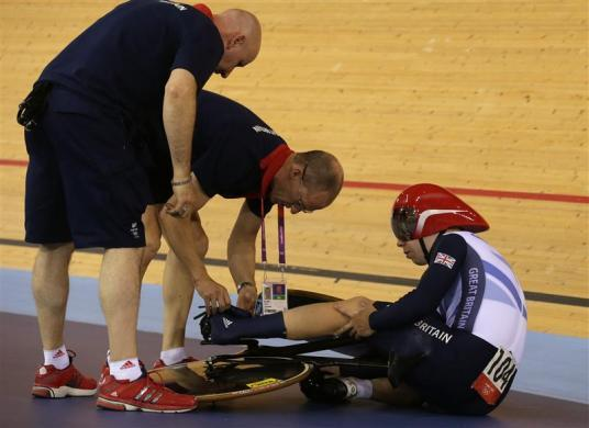 Britain's Philip Hindes sits on the ground after falling during their track cycling men's team sprint qualifying heats at the Velodrome during the London 2012 Olympic Games August 2, 2012. The officials had to assist Hindes as his left foot remained clipped in after the fall.