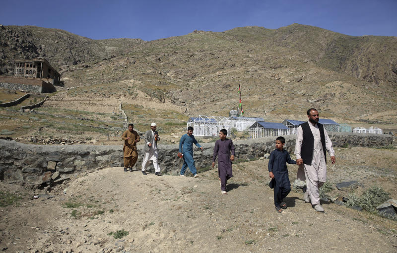 In this Wednesday, May 20, 2020 photo, members of the Aryubi family walk to a graveyard where Dr. Yousuf Aryubi and two siblings who lost their lives to COVID-19 are buried, in Kabul, Afghanistan. Dr. Aryubi's family assumed they just had a bad cold, as one after another, they came down with fevers and coughs -- all because one of the Afghan capital's main hospitals never told them the results of his coronavirus test. Their tragedy points to how a broken-down health system, slow government response and public attitudes have left Afghanistan deeply vulnerable to the global pandemic. (AP Photo/Rahmat Gul)
