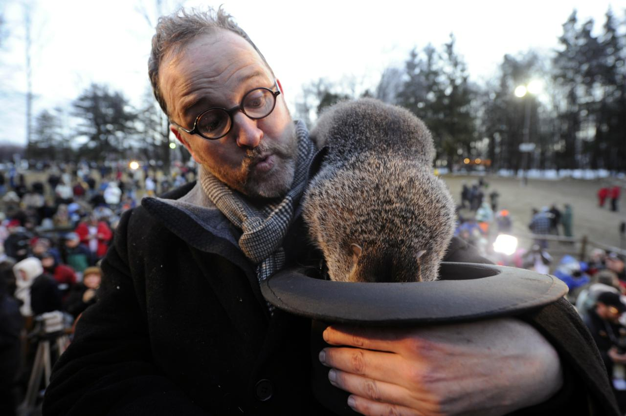 PUNXSUTAWNEY, PA - FEBRUARY 2:  Groundhog handler Ben Hughes watches Punxsutawney Phil after he did not see his shadow predicting an early spring during the 125th annual Groundhog Day festivities on February 2, 2011 in Punxsutawney, Pennsylvania. Groundhog Day is a popular tradition in the United States and Canada. A smaller than usual crowd this year of less than 15,000 people spent a night of revelry awaiting the sunrise and the groundhog's exit from his winter den. If Punxsutawney Phil sees his shadow he regards it as an omen of six more weeks of bad weather and returns to his den. Early spring arrives if he does not see his shadow causing Phil to remain above ground.  (Photo by Jeff Swensen/Getty Images)