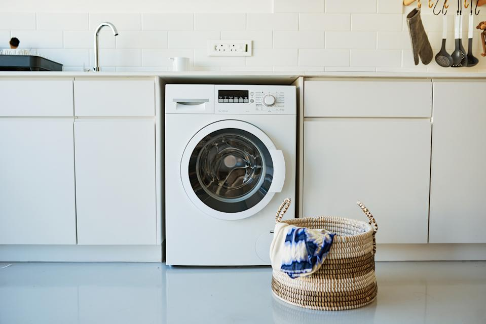 Shot of a laundry basket standing in front of a washing machine
