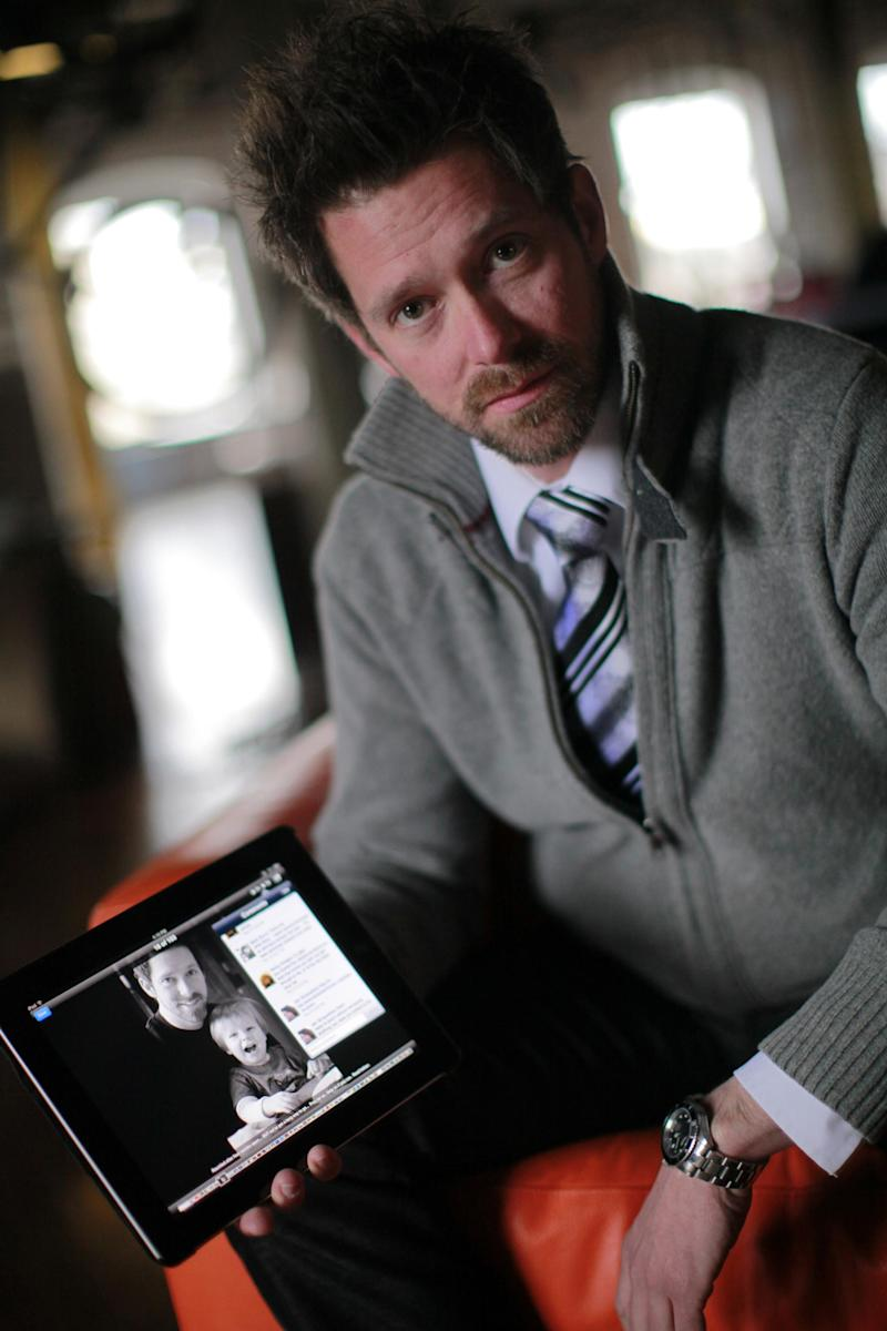 FILE - In this Tuesday, Feb. 21, 2012 file photo, Mark Byron, a local photographer, holds his iPad with a photo of himself and his son, in his studio in Cincinatti, Ohio. Byron, who made comments about his estranged wife on his Facebook page and was threatened with jail unless he posted daily apologies for a month, won't be locked up even though he stopped making amends early. (AP Photo/The Enquirer, Liz Dufour, File)  NO SALES