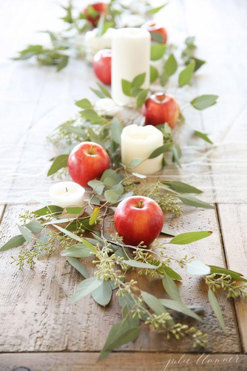 """<p>We love the idea of incorporating the fall harvest in your Thanksgiving tablescape. Freshly-picked apples, leaves and branches cut from your own backyard, and a few pillar candles work together to create a look that's as elegant as it is inexpensive.</p><p><strong>Get the tutorial at <a href=""""https://julieblanner.com/easy-entertaining-ideas-for-fall/"""" rel=""""nofollow noopener"""" target=""""_blank"""" data-ylk=""""slk:Julie Blanner"""" class=""""link rapid-noclick-resp"""">Julie Blanner</a>.</strong></p><p><a class=""""link rapid-noclick-resp"""" href=""""https://www.amazon.com/Mega-Candles-Unscented-Receptions-Celebrations/dp/B00ATGA136?tag=syn-yahoo-20&ascsubtag=%5Bartid%7C10050.g.2130%5Bsrc%7Cyahoo-us"""" rel=""""nofollow noopener"""" target=""""_blank"""" data-ylk=""""slk:SHOP WHITE CANDLES"""">SHOP WHITE CANDLES</a></p>"""