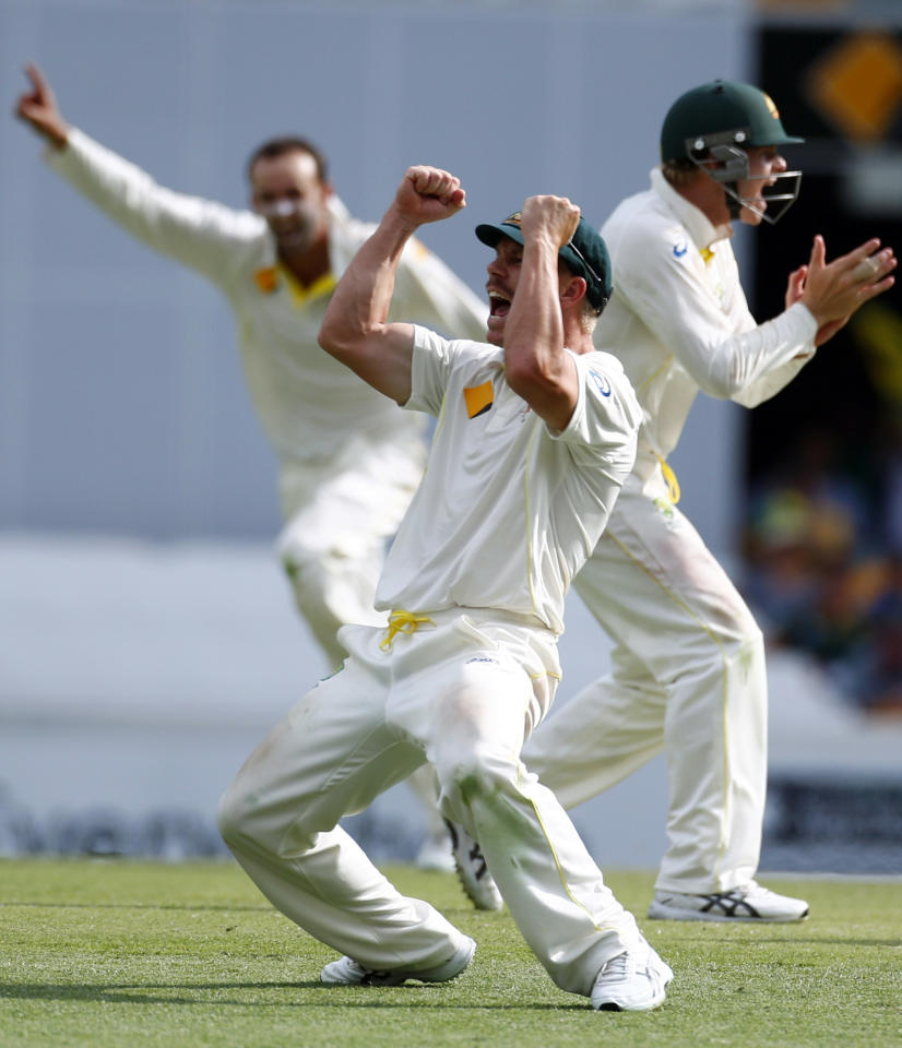 Australia's David Warner (front) celebrates after he took the catch to dismiss England's Matt Prior during the fourth day's play of the first Ashes cricket test match in Brisbane November 24, 2013. REUTERS/David Gray (AUSTRALIA - Tags: SPORT CRICKET)