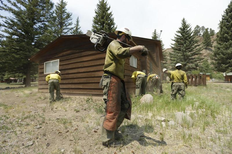 Firefighters from the San Juan Hotshots based in Durango, Colo, clear brush from around structures Saturday, June 22, 2013, in South Fork, Colo. Fire crews with tankers and hoses stood guard Friday night as a massive and fast-burning wildfire threatened a popular mountain tourist enclave in southwestern Colorado, forcing the evacuation of more than 400 people. (AP Photo/Gregory Bull)