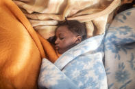 5-year old Timi sleeps between the blankets at her mother's feet, basking in the warmth of the sun's rays after being rescued in the Mediterranean Sea, international waters by the Spanish NGO Open Arms rescue vessel, Sunday, Feb. 14, 2021. Various African migrants drifting in the Mediterranean Sea after fleeing Libya on unseaworthy boats have been rescued. In recent days, the Libyans had already thwarted eight rescue attempts by the Open Arms, a Spanish NGO vessel, harassing and threatening its crew in international waters. Various African migrants drifting in the Mediterranean Sea after fleeing Libya on unseaworthy boats have been rescued. In recent days, the Libyans had already thwarted eight rescue attempts by the Open Arms, a Spanish NGO vessel, harassing and threatening its crew in international waters. (AP Photo/Bruno Thevenin)