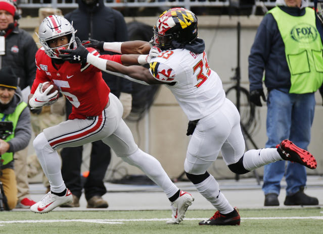Ohio State receiver Garrett Wilson, left, stiff arms Maryland defensive back Deonte Banks during the first half of an NCAA college football game, Saturday, Nov. 9, 2019, in Columbus, Ohio. (AP Photo/Jay LaPrete)