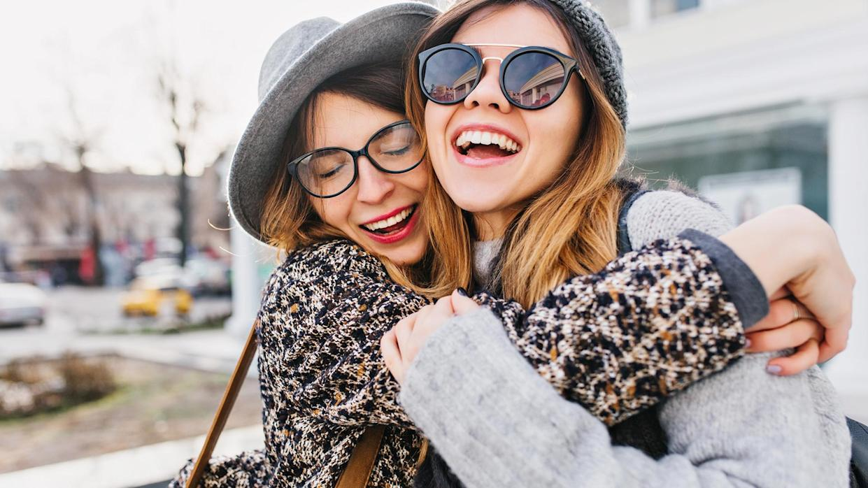 Happy brightful positive moments of two stylish girls hugging on street in city.