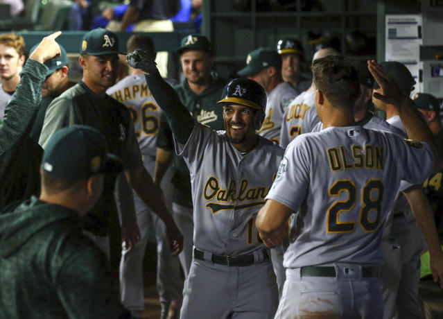 Oakland Athletics shortstop Marcus Semien (10) is greeted in the dugout after a solo home run in the ninth inning that broke the tie against the Texas Rangers in a baseball game Monday, April 23, 2018, in Arlington, Texas. (AP Photo/Richard W. Rodriguez)