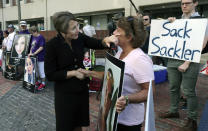 FILE - In this Friday, Aug. 2, 2019 file photo, Massachusetts Attorney General Maura Healey, left, wipes a tear from the face of Wendy Werbiskis, of East Hampton, Mass., one of the protesters gathered outside a courthouse in Boston, where a judge was to hear arguments in state's lawsuit against Purdue Pharma over its role in the national drug epidemic. The end of the Purdue Pharma bankruptcy case has left a bitter taste for those who wanted to see more accountability for the Sackler family. They will pay more than $4 billion under the settlement but also will escape any future liability over the nation's opioid crisis. (AP Photo/Charles Krupa, File)