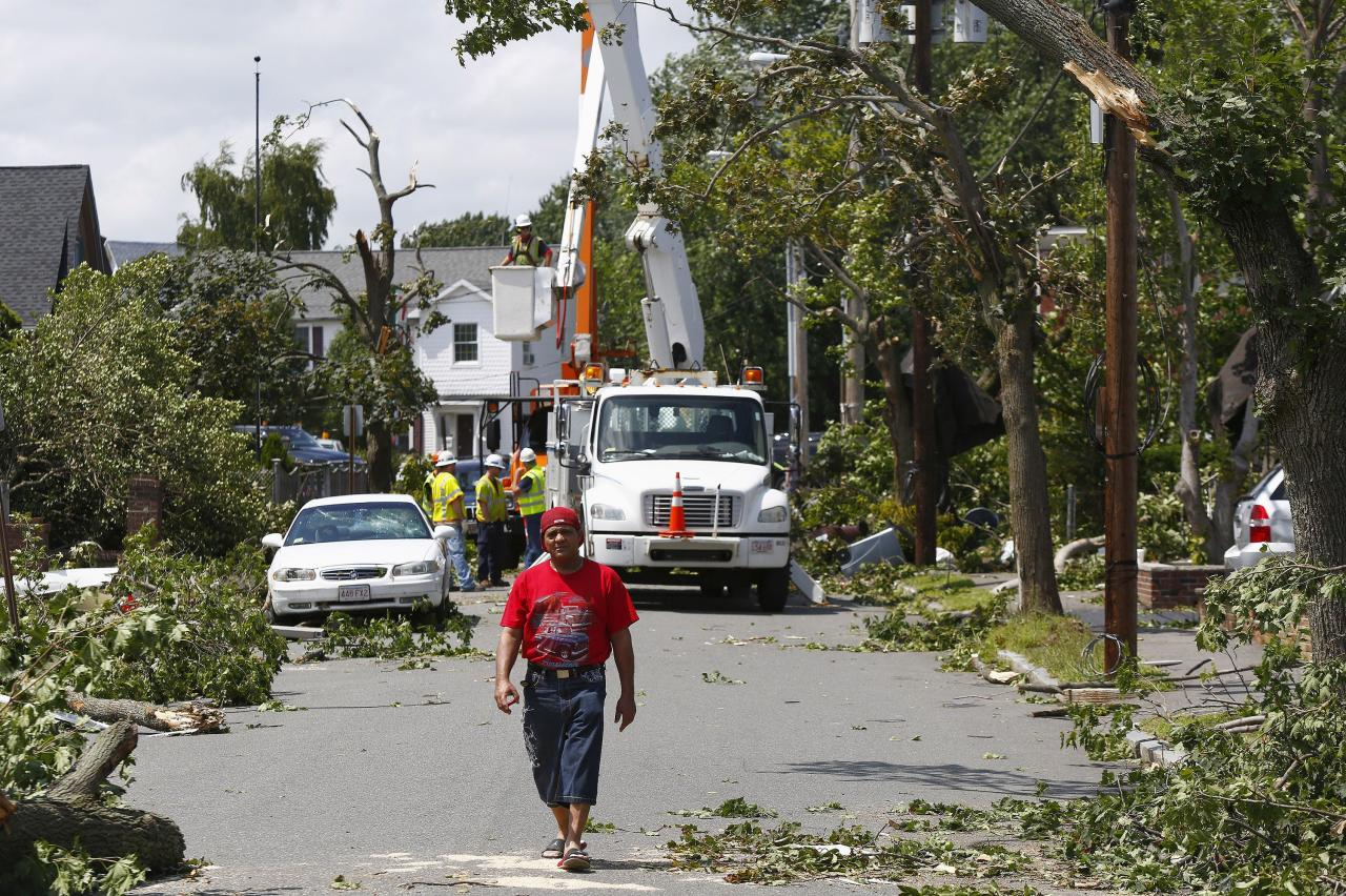 A man walks amid cleanup crews on Vinal Street in Revere, Massachusetts, July 28, 2014. Police and emergency crews in Revere, outside Boston scrambled to clean up after a rare tornado touched down on Monday, downing power lines, damaging homes and overturning at least one car. The National Weather Service confirmed that a tornado touched down during a storm that brought heavy rains, lightning and flooding to Boston and many of its northern suburbs. State emergency management officials said they were not aware of major injuries or fatalities from the storm. REUTERS/Dominick Reuter (UNITED STATES - Tags: ENVIRONMENT DISASTER SOCIETY)