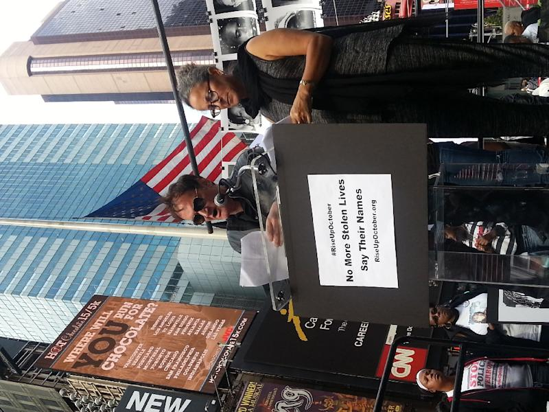 Film director Quentin Tarantino and actress Gina Belafonte read out the names of people who have died at the hands of police at a rally demanding an end to police brutality in New York's Times Square on October 22, 2015 (AFP Photo/Jennie Matthew)