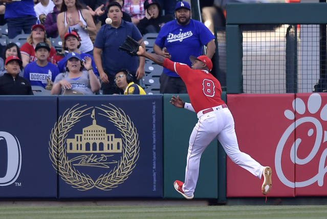 Los Angeles Angels left fielder Justin Upton tries to field a ball hit for an RBI double by Los Angeles Dodgers' Max Muncy during the first inning of a preseason baseball game Sunday, March 24, 2019, in Anaheim, Calif. Upton was injured on the play and was taken out of the game. (AP Photo/Mark J. Terrill)