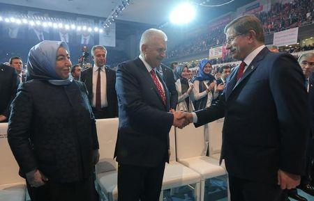 Transportation Minister Yildirim shakes hands with Turkey's outgoing Prime Minister Davutoglu during the AKP extraordinary congress in Ankara
