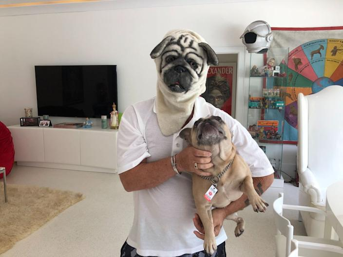 George Buff wears a pug mask and holds his bulldog at home in Palm Beach.
