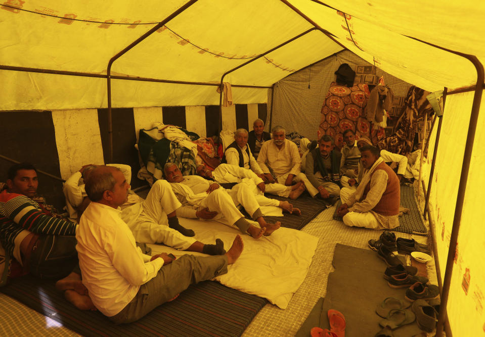 Farmers sit in their makeshift tent on the highway as they continue to protest against new farm laws at the Delhi-Uttar Pradesh border, on the outskirts of New Delhi, India, Saturday, Jan. 30, 2021. Indian farmers and their leaders spearheading more than two months of protests against new agriculture laws began a daylong hunger strike Saturday, directing their fury toward Prime Minister Narendra Modi and his government. Farmer leaders said the hunger strike, which coincides with the death anniversary of Indian independence leader Mahatma Gandhi, would reaffirm the peaceful nature of the protests. (AP Photo/Manish Swarup)