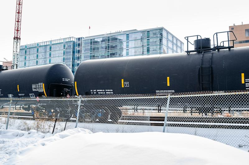 Tank Railcars in a Snowy Cargo Train Terminal with Buildings in Background. Calgary, AB, Canada.