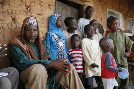 The leader of the displaced Fulani herdsmen Haruna Usman (L) sits next to children from his tribe during an exclusive interview with Reuters in Barkin Kogi, Zango Kataf, Kaduna State March 22, 2014. Picture taken March 22, 2014. REUTERS/Afolabi Sotunde