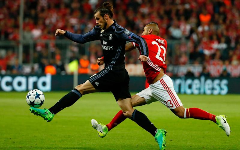 Real Madrid's Welsh forward Gareth Bale (L) and Bayern Munich's Chilean midfielder Arturo Vidal vie for the ball during the UEFA Champions League 1st leg quarter-final football match FC Bayern Munich v Real Madrid - Credit: AFP