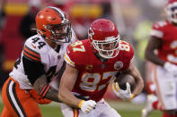 Kansas City Chiefs tight end Travis Kelce (87) tries to break a tackle by Cleveland Browns linebacker Sione Takitaki (44) after catching a pass during the second half of an NFL divisional round football game, Sunday, Jan. 17, 2021, in Kansas City. (AP Photo/Charlie Riedel)