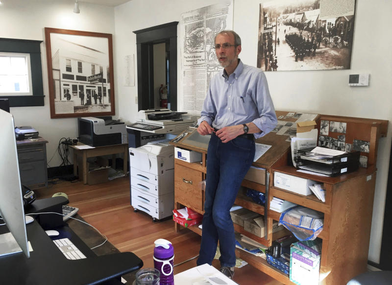 This May 29, 2019 photo shows Larry Persily, the publisher of The Skagway News, in the newspaper office in Skagway, Alaska. If you've ever wanted to own a small bi-weekly newspaper in Alaska but didn't have the money, this could be your chance. The publisher of The Skagway News is willing to give the paper away to the right person, if they are willing to move to the southeast Alaska community and be a part of the community. Persily says he's willing to help out the new owners by giving away the paper because the advertising will afford them a living wage, but not on top of a mortgage. (Molly McCammon via AP)