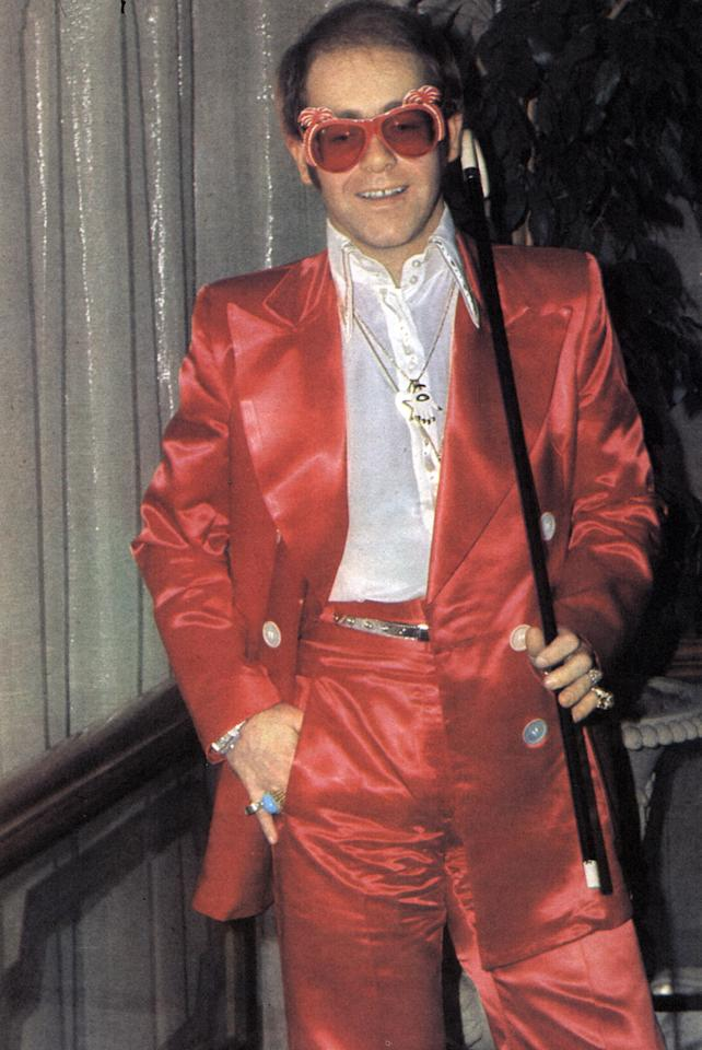 <p>Elton John in shiny red suit, pink glasses, and cane in 1973. (Photo: Getty Images) </p>