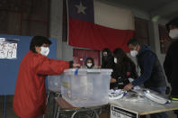 A woman votes at a polling station in Santiago, Chile, Sunday, Oct. 25, 2020. Amid a year of contagion and turmoil, Chileans vote Sunday on whether to draft a new constitution for their nation to replace guiding principles imposed four decades ago under a military dictatorship.(AP Photo/Esteban Felix)