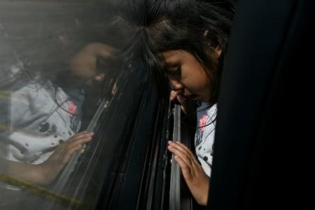 FILE PHOTO: A migrant girl from Guatemala recently released with her mother from federal detention sits on a bus before its departure from a bus depot in McAllen