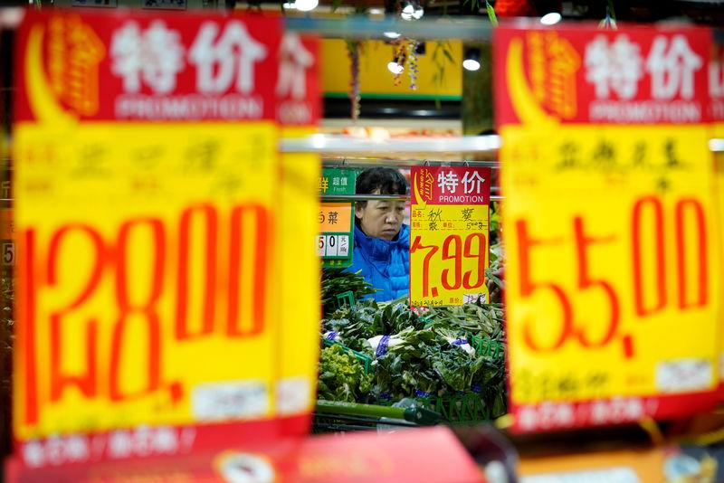 FILE PHOTO: A woman selects vegetables at a supermarket in Beijing