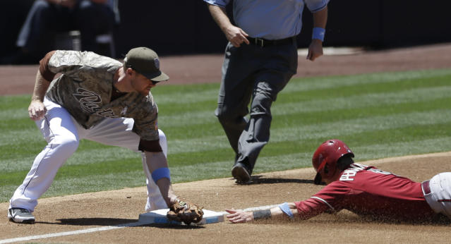 San Diego Padres third baseman Chase Headley, left, applies a late as Arizona Diamondbacks' Cliff Pennington, right, safely steals third base during the third inning in a baseball game on Sunday, June 16, 2013, in San Diego. (AP Photo/Gregory Bull)