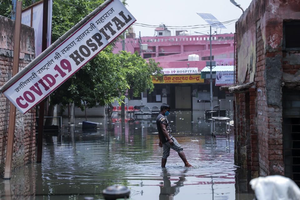 A worker tries to clear water after heavy rains flooded the premises of a COVID-19 hospital being set up at Ghaziabad, outskirts of New Delhi, India, Sunday, May 23, 2021. The hospital is not functional yet. (AP Photo/Amit Sharma)