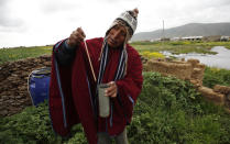 In this Feb. 14, 2014 photo, farmer and traditional meteorologist Francisco Condori measures rain water with a flow meter in Cutusuma, on Lake Titicaca's southern shore in Bolivia. Condori is a well-heeded font of ancestral knowledge for fellow farmers in these treeless climes frequently punished by frosts, hailstorms and drought. (AP Photo/Juan Karita)