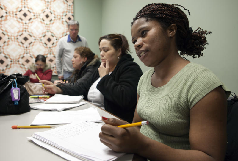 In this photo taken March 16, 2012, immigrant Martha Johnson from Liberia, right, attends and American history and civic class in Chelsea, Mass., in preparation for a naturalization test.Hundreds of volunteers are helping qualified immigrants become U.S. citizens in time to register to vote in the November presidential elections. (AP Photo/Rodrique Ngowi)