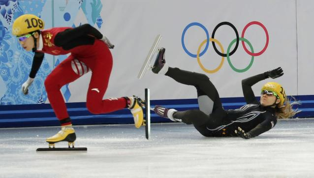 China's Kexin Fan (L) speeds past Jessica Smith (R) of the United States who crashes out while competing in the women's 500 metres short track speed skating heats event at the Iceberg Skating Palace during the 2014 Sochi Winter Olympics February 10, 2014. REUTERS/Alexander Demianchuk (RUSSIA - Tags: SPORT SPEED SKATING OLYMPICS)