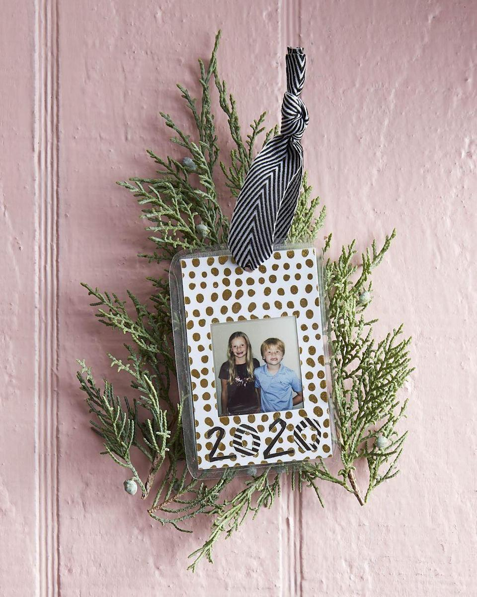"""<p>Long-lasting thanks to lamination, this ornament freezes a moment in time. Drop it in the mail to show far-flung relatives how big the littles are getting.</p><p><strong>To make:</strong> Cut two pieces of decorative craft paper to desired size. Cut a hole (it can be any shape) in one piece of the craft paper that is just smaller than the photo. Tape the photo over the opening. Tape the second piece of paper to the back with double-stick tape (this hides the messy back). Use sticker numbers or cut out numbers from craft paper and glue them to the paper below the picture. Run the ornament through a laminator; round edges. Punch a hole in the top; thread a ribbon through the hole to hang.</p><p><a class=""""link rapid-noclick-resp"""" href=""""https://www.amazon.com/Scotch-Thermal-Laminator-Professional-Laminate/dp/B0010JEJPC/ref=sr_1_4?tag=syn-yahoo-20&ascsubtag=%5Bartid%7C10050.g.645%5Bsrc%7Cyahoo-us"""" rel=""""nofollow noopener"""" target=""""_blank"""" data-ylk=""""slk:SHOP LAMINATING MACHINES"""">SHOP LAMINATING MACHINES</a></p>"""