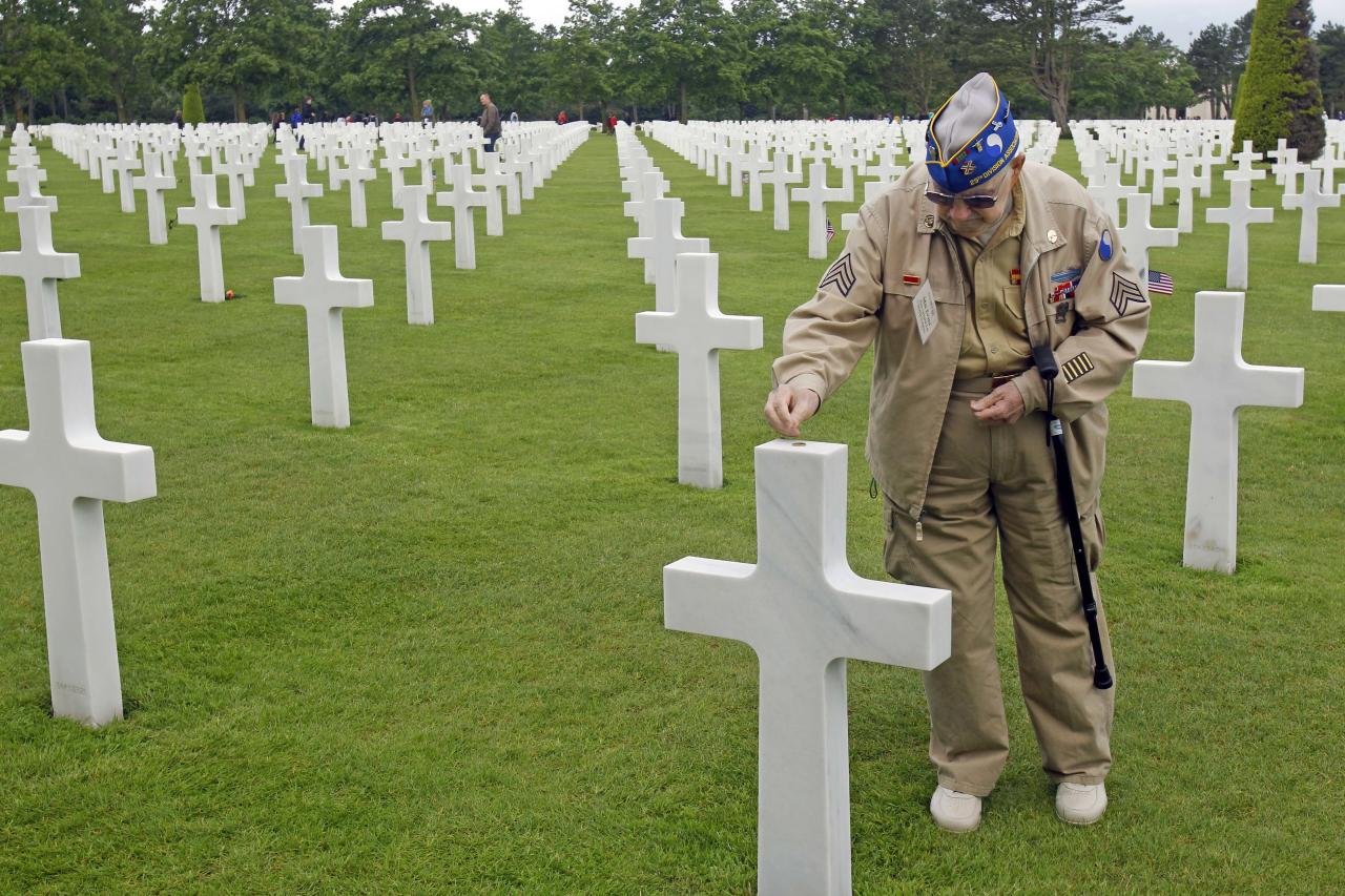 U.S. WW II veteran Clarence Mac Evans, 87, from West Virginia, who landed in Normandy on June 6, 1944, with the 29th infantery division, puts a coin on the tomb of fellow Franck Nuzzo, from the 29th division who died on June 6, 1944, at the Colleville American military cemetery.(AP Photo/Remy de la Mauviniere)