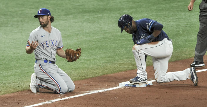 Texas Rangers' Charlie Culberson, left, looks to the Texas dugout after Tampa Bay Rays' Manuel Margot, right, stole third base during the fourth inning of a baseball game Thursday, April 15, 2021, in St. Petersburg, Fla. (AP Photo/Steve Nesius)