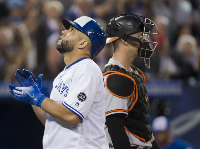 Toronto Blue Jays designated hitter Kendrys Morales, left, reacts after hitting a solo home run against the Baltimore Orioles during fourth-inning baseball game action in Toronto, Monday, Aug. 20, 2018. (Nathan Denette/The Canadian Press via AP)