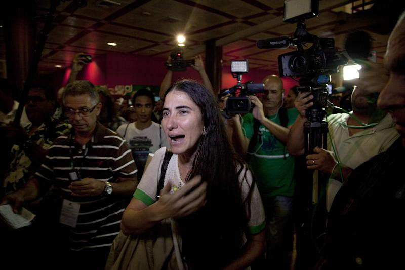 Cuban dissident blogger Yoani Sanchez is surrounded by journalists upon her arrival at the Jose Marti International Airport in Havana, Cuba, Thursday, May 30, 2013. Sanchez is back home after a more than three-month globe-trotting tour that has turned her into the most internationally recognizable face in the island's small dissident community. Sanchez has been on the road since Feb. 17 and visited more than a dozen countries in Europe and the Americas. (AP Photo/Ramon Espinosa)