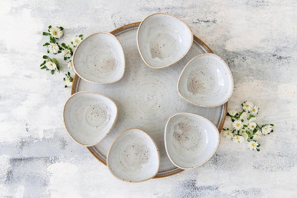 """<p>Nora Fuksman's handmade work of art would be a beautiful addition to your Seder table with its six teardrop-shaped ceramic bowls that match perfectly with the round serving plate. Choose a minimalist white or any modern hue in her palette including green, turquoise, blue, or """"banana yellow.""""</p> <p><em><strong>Shop Now:</strong></em> <em>Nora Pottery Art</em> <em>Seder Plate, $216, <a href=""""https://www.awin1.com/cread.php?awinmid=6220&awinaffid=272513&clickref=MSL10PassoverSederPlatesGuaranteedtoBecomeYourNextFamilyHeirloomachurchiPasGal8067612202103I&p=https%3A%2F%2Fwww.etsy.com%2Flisting%2F562433106%2Fpottery-wedding-gift-passover-jewish"""" rel=""""sponsored noopener"""" target=""""_blank"""" data-ylk=""""slk:norapotteryart.etsy.com"""" class=""""link rapid-noclick-resp"""">norapotteryart.etsy.com</a>.</em></p>"""