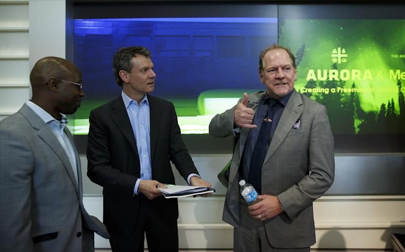 Terry Booth, chief executive officer of Aurora Cannabis Inc., right, gestures while speaking with Cam Battley, chief corporate officer of Aurora Cannabis Inc., center, during a news conference at the Toronto Stock Exchange (TSX) in Toronto, Ontario, Canada, on Monday, May 14, 2018. Aurora Cannabis Inc. agreed to buy rival MedReleaf Corp. for about C$2.9 billion ($2.3 billion) in stock, the companies said Monday in a statement. The deal will create a producer with the capacity to grow 570,000 kilos (1.26 million pounds) a year of cannabis at nine facilities in Canada and two in Denmark. Photographer: Cole Burston/Bloomberg via Getty Images