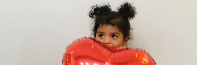 A little girl sitting on floor and holding a red balloon
