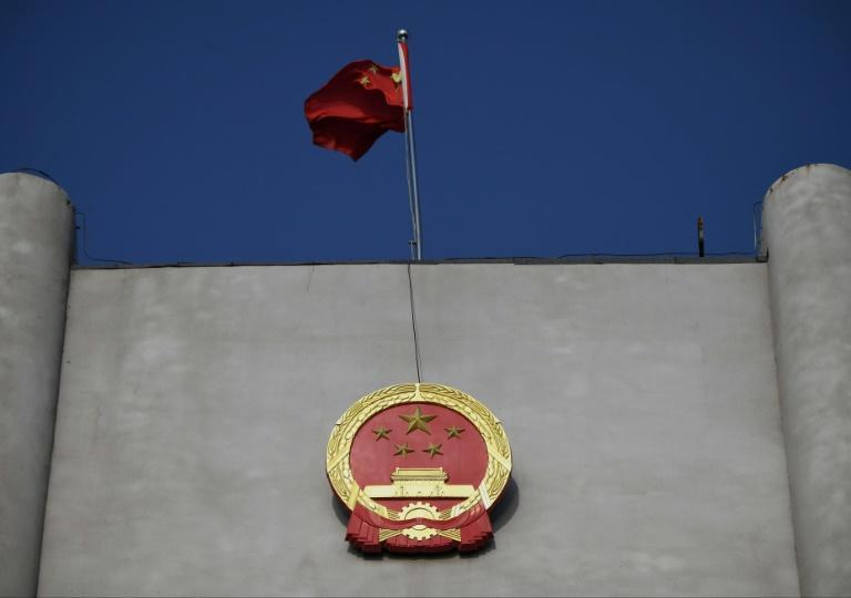 China's national flag flies at a court where a Canadian national's trial has opened on espionage charges
