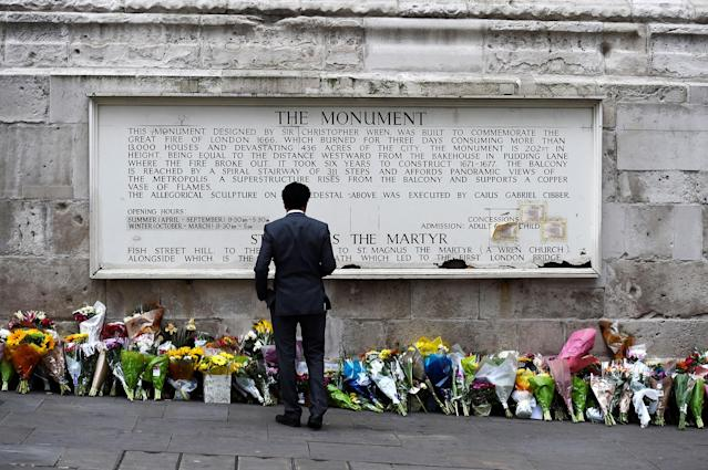 <p>A man observes flowers left along the base of the Monument to the Great Fire of London near London Bridge after an attack on the bridge and nearby Borough Market left 7 dead and dozens injured, in London, Britain, June 5, 2017. (Photo: Clodagh Kilcoyne/Reuters) </p>