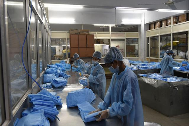 Workers check surgical gowns at a production facility in the outskirts of Ahmedabad.