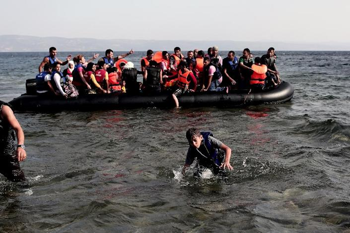Refugees from Syria arrive on the shores of the Greek island of Lesbos aboard an inflatable dinghy, after crossing the Aegean Sea from Turkey, September 7, 2015 (AFP Photo/Angelos Tzortzinis)